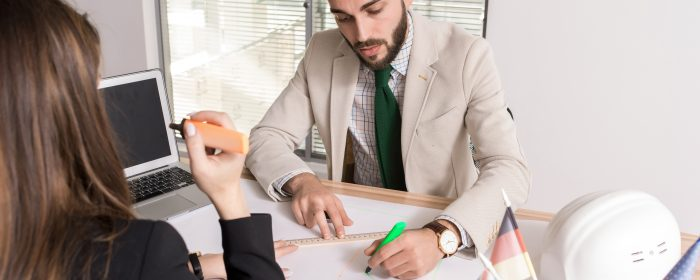 Portrait of two business people drafting plans sitting at desk in international agency